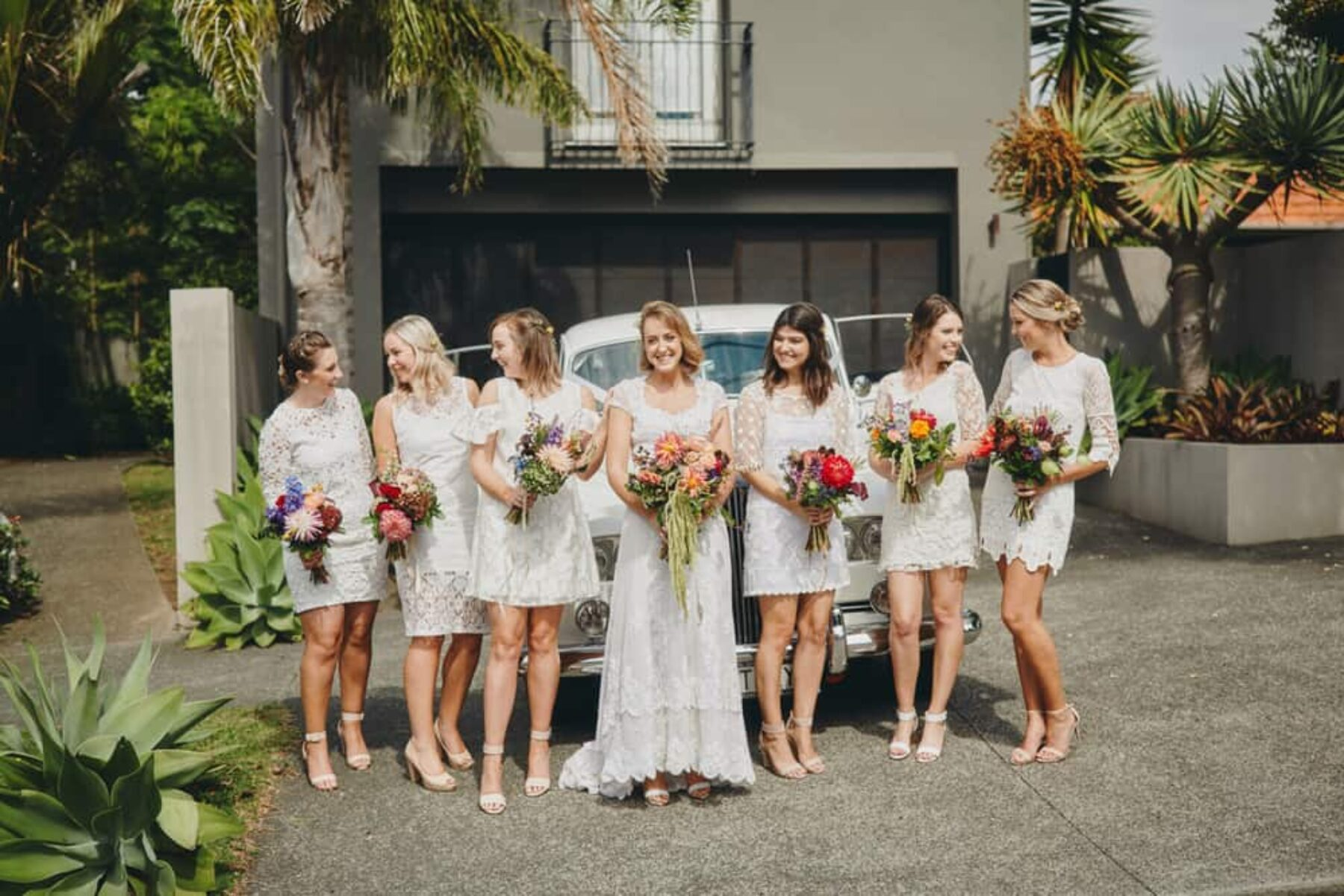 Bridesmaids in white with vibrant bouquets