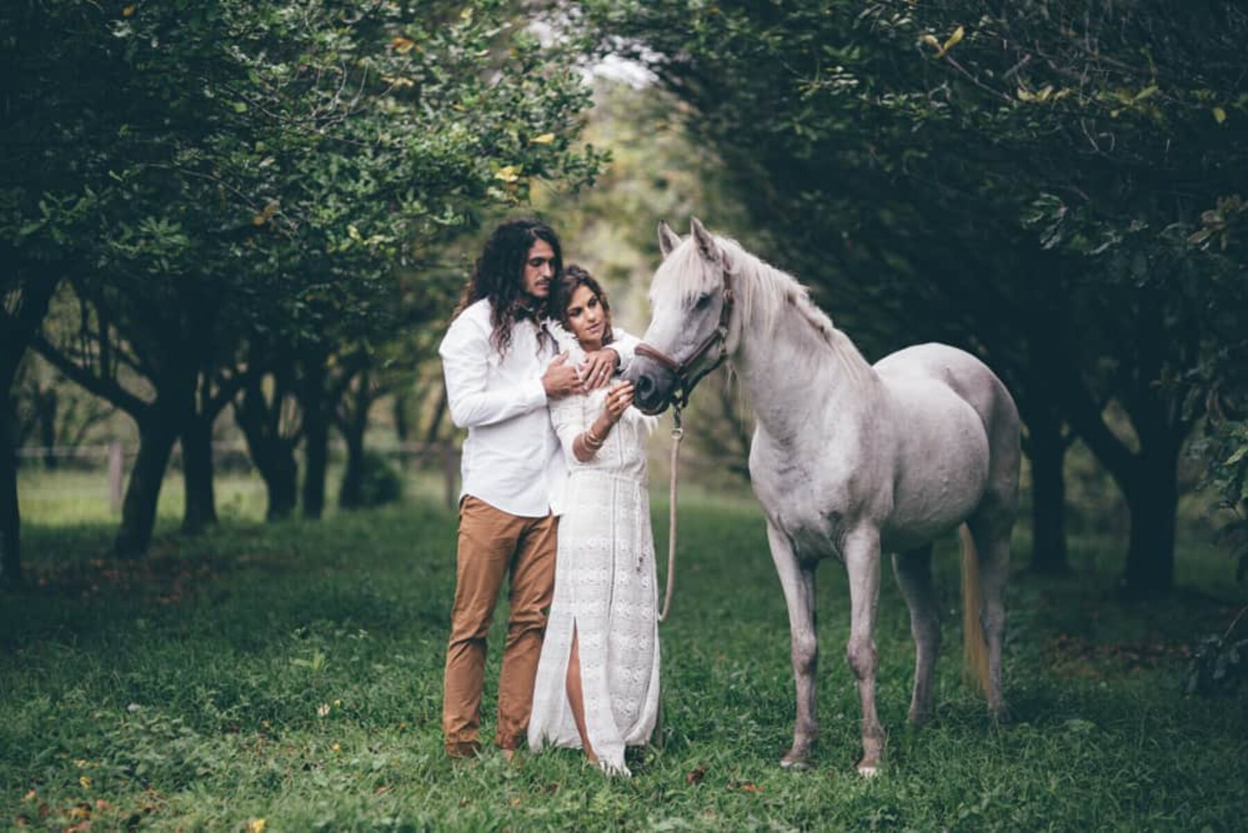 boho bride and groom with white horse