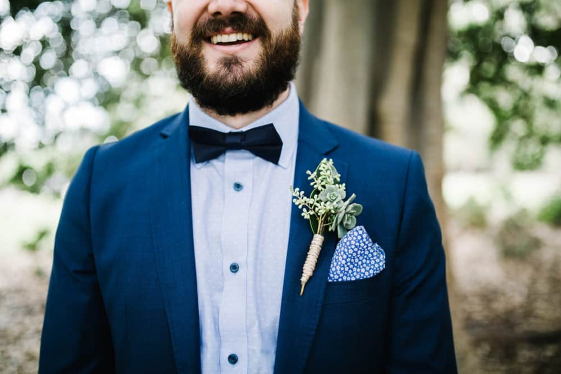 groom in cobalt suit with succulent boutonniere