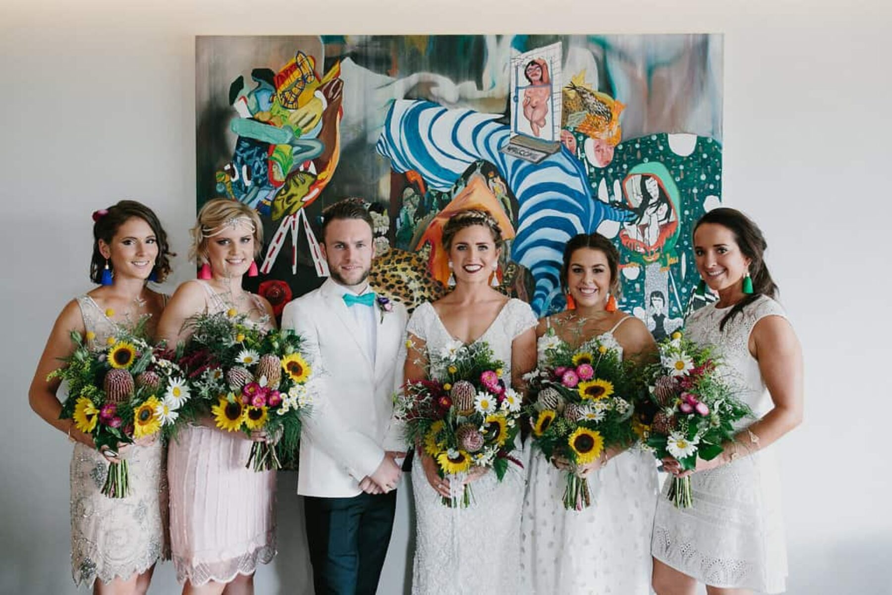 bride, bridesmaids and bridesman with colouful bouquets
