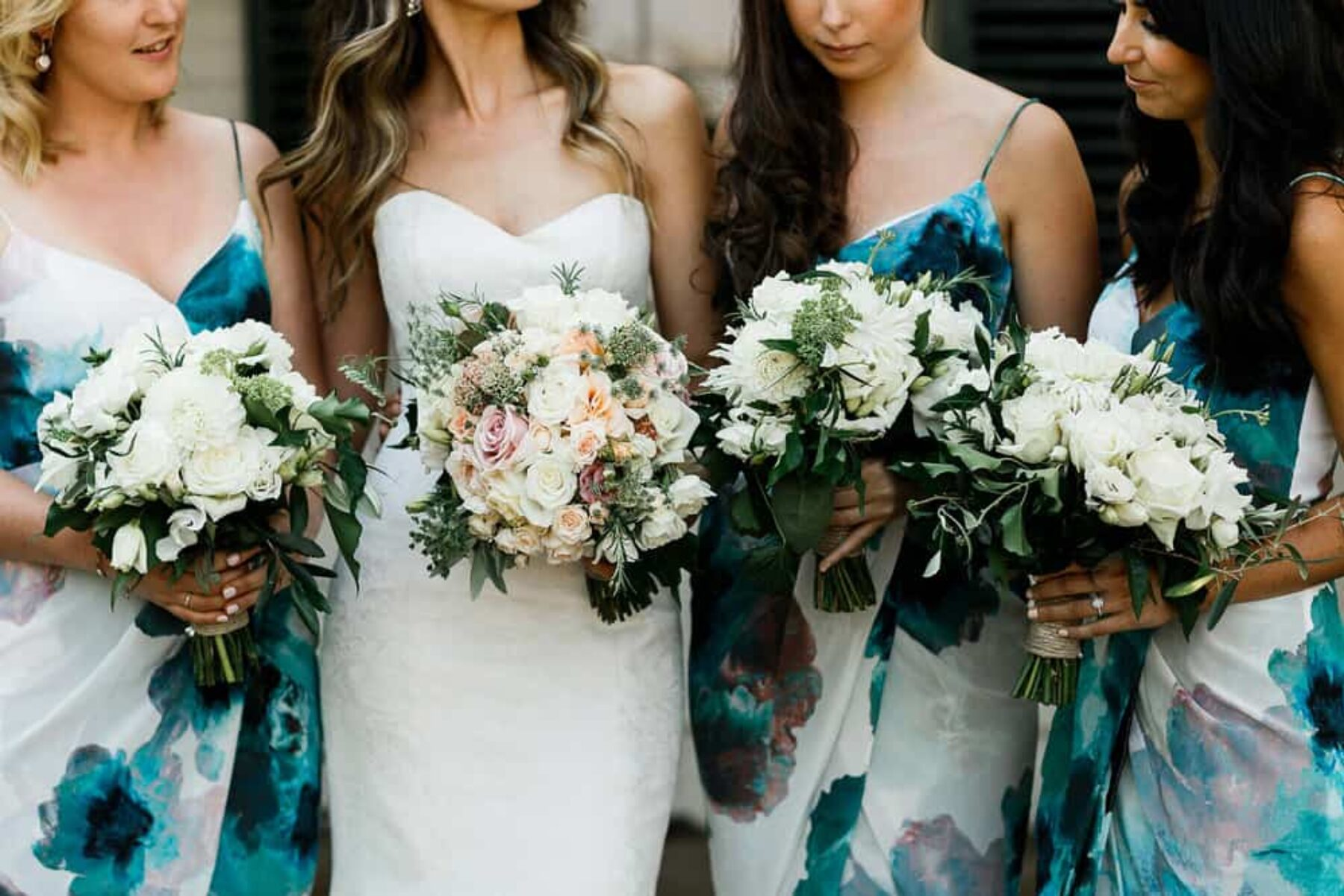 bridesmaids in blue floral print dresses and classic bouquets