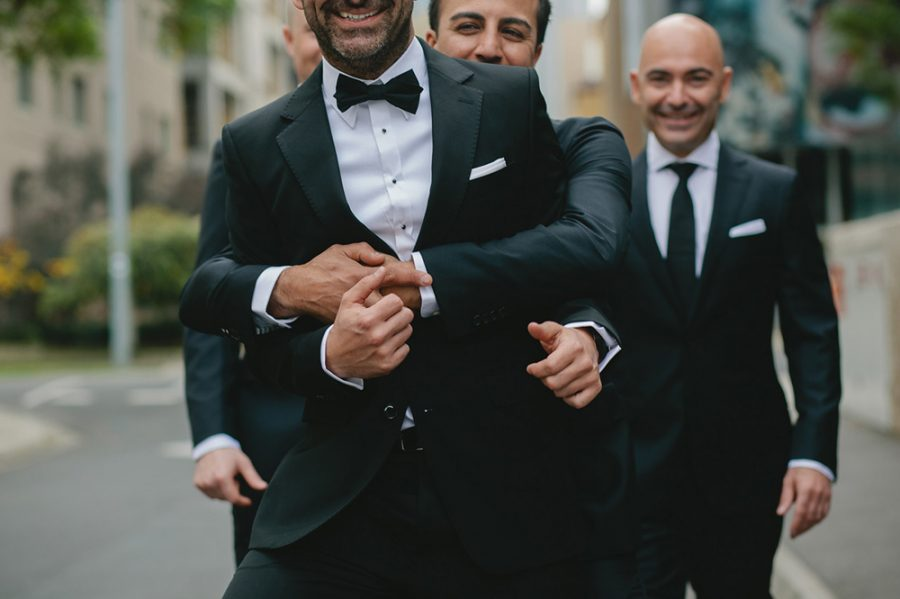 Groomsmen in black suits from Calibre