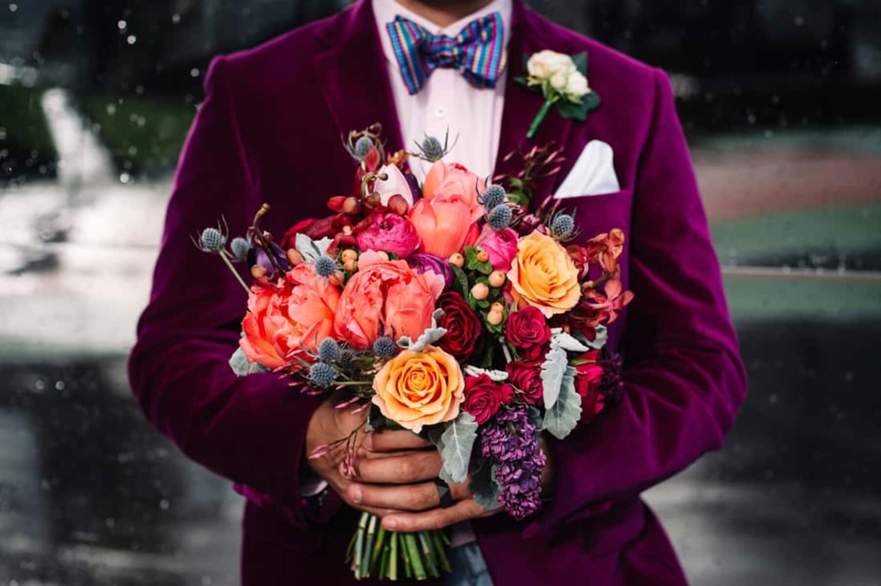 stylish groom in magenta velvet blazer with peach bouquet
