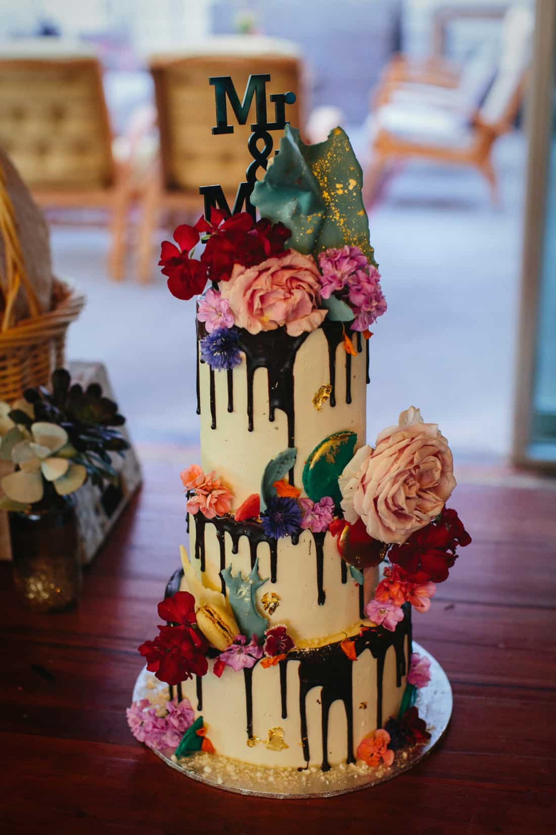 creative three-tier wedding cake with chocolate drip