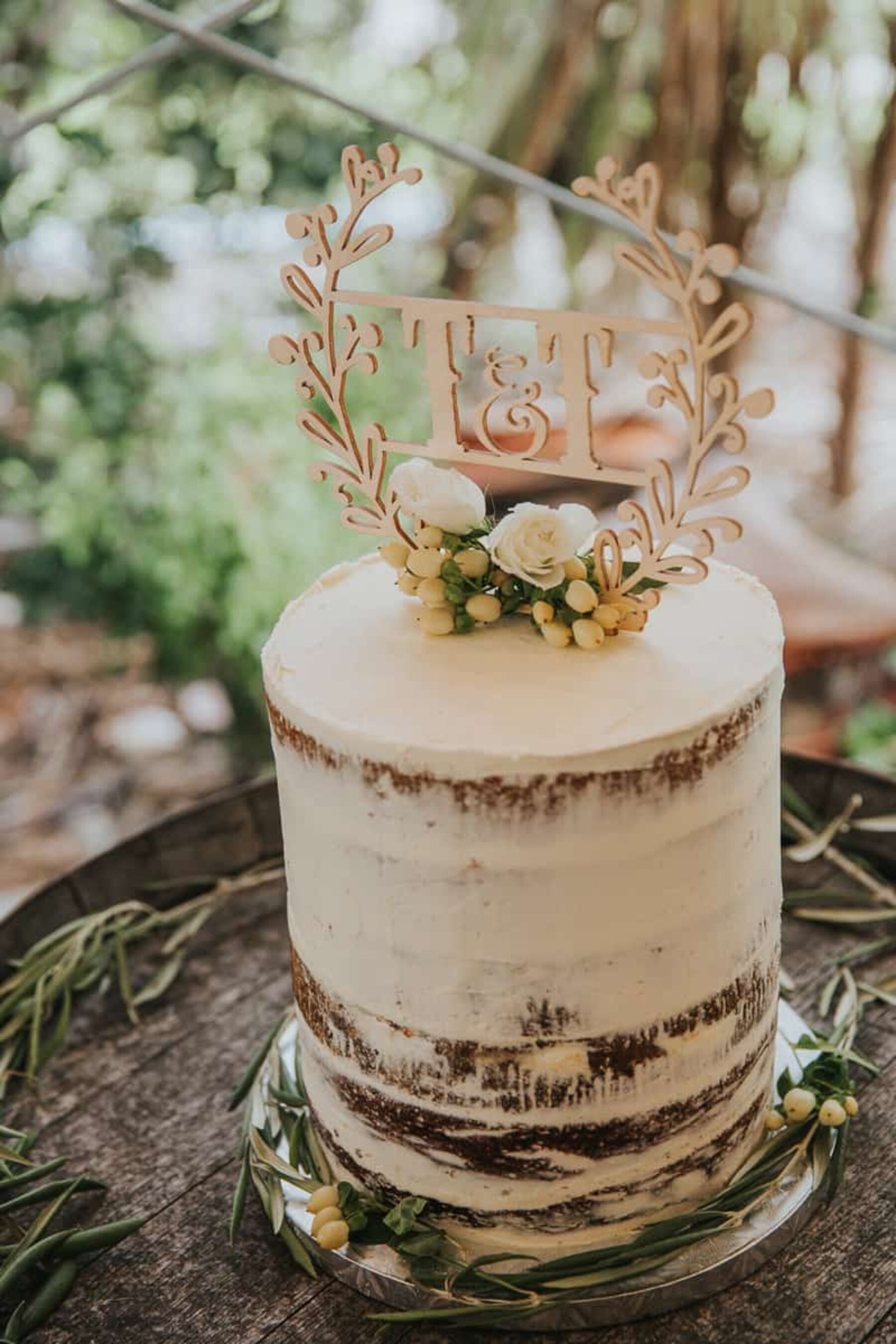 semi-naked wedding cake with wooden monogram topper