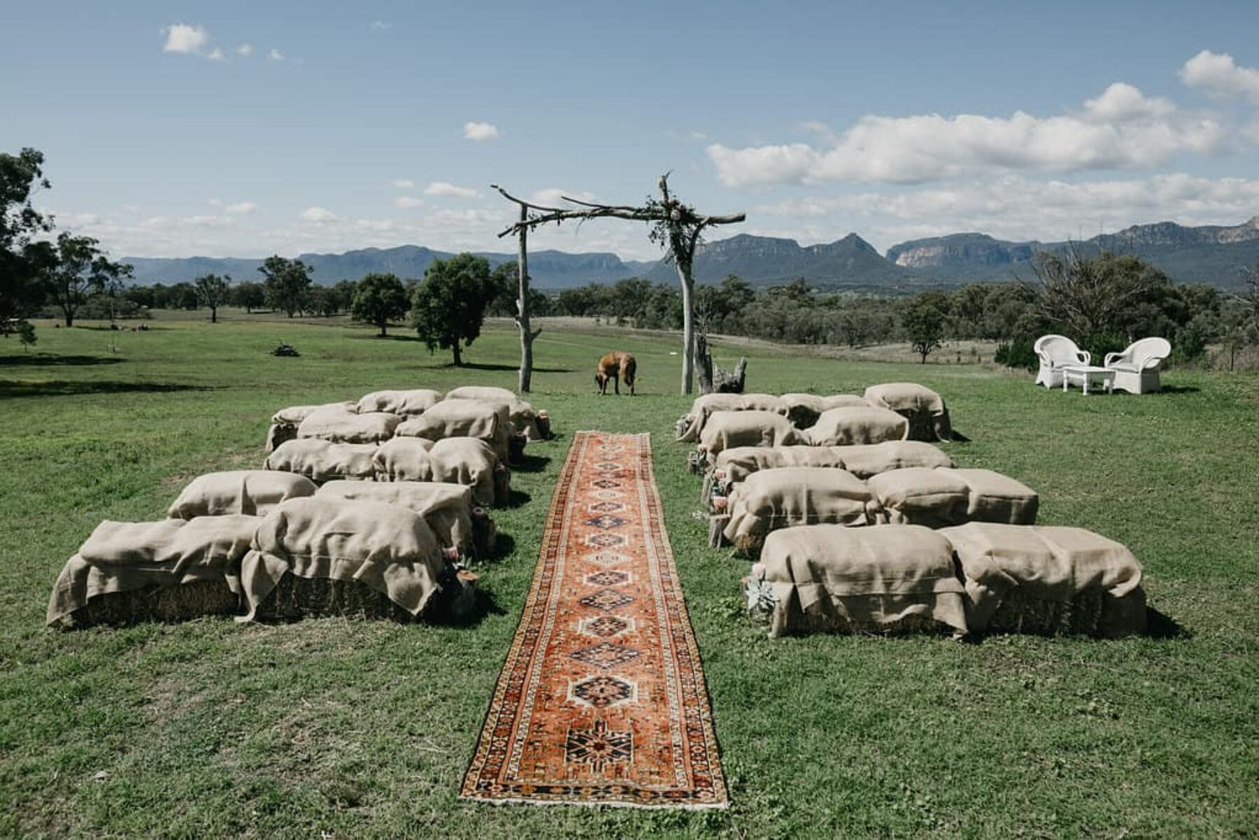 farm wedding backdrop with hay bales and Persian rug runner