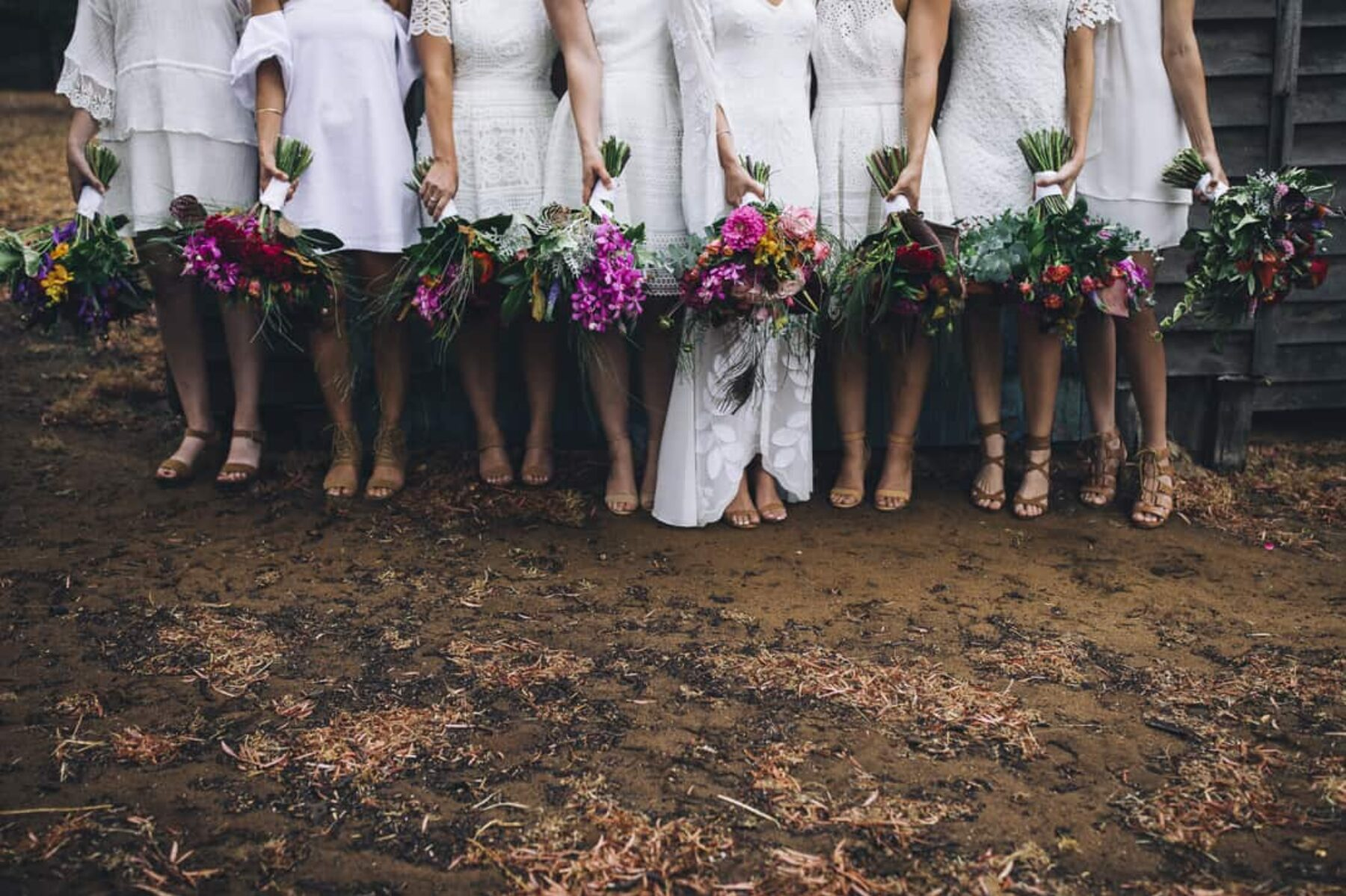 boho bridesmaids in mixed white dresses with vibrant bouquets