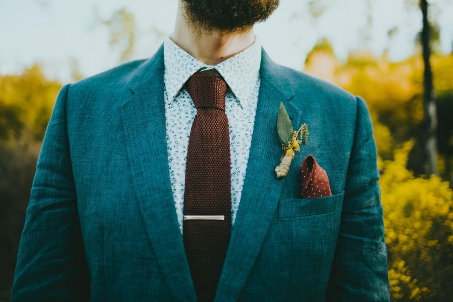 hipster groom with floral shirt and knitted tie
