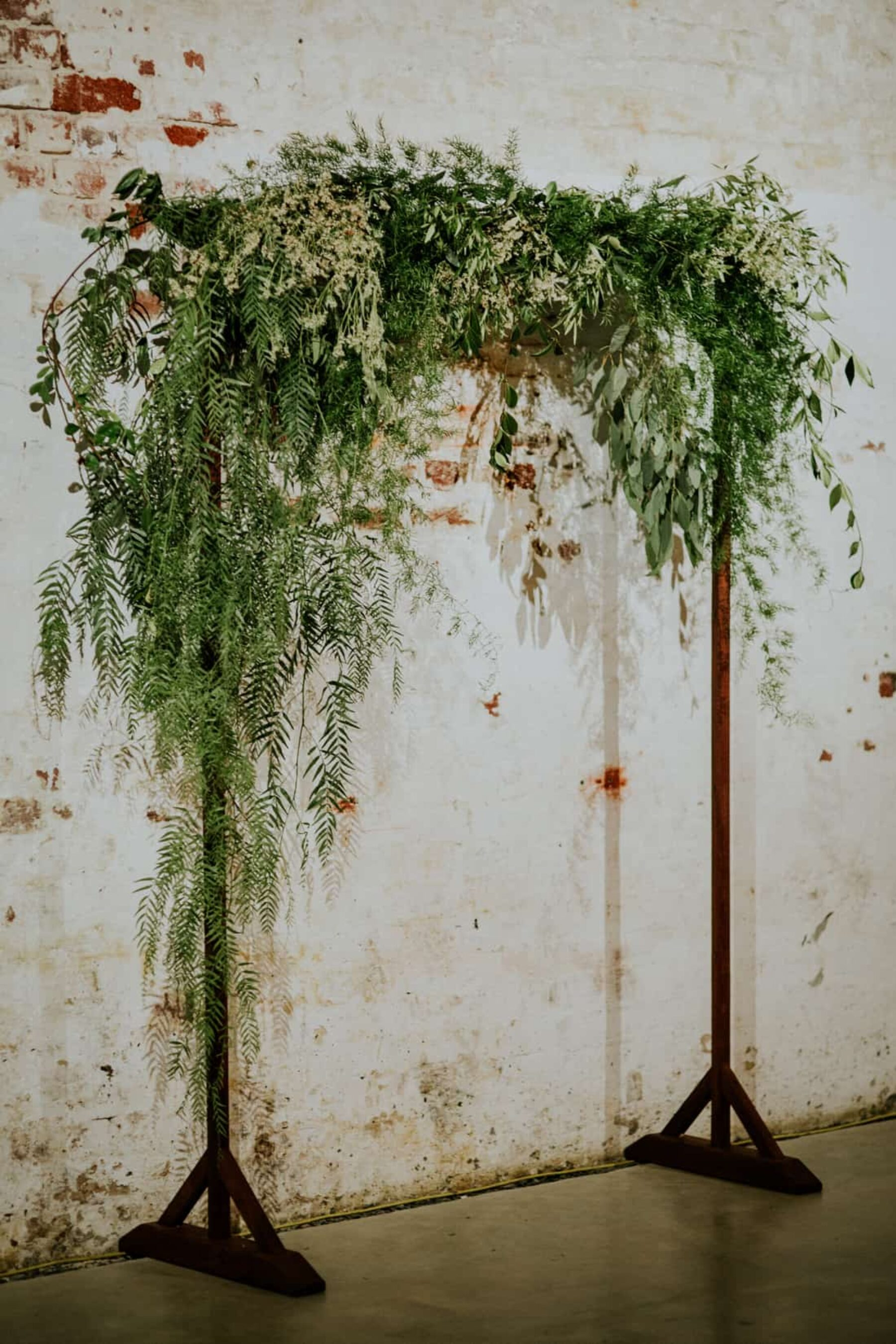 industrial wedding with greenery arbour