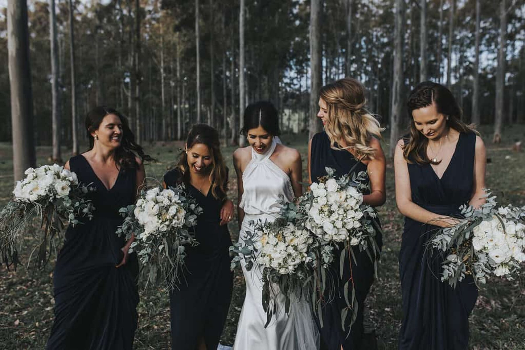 navy bridesmaids with green and white bouquets