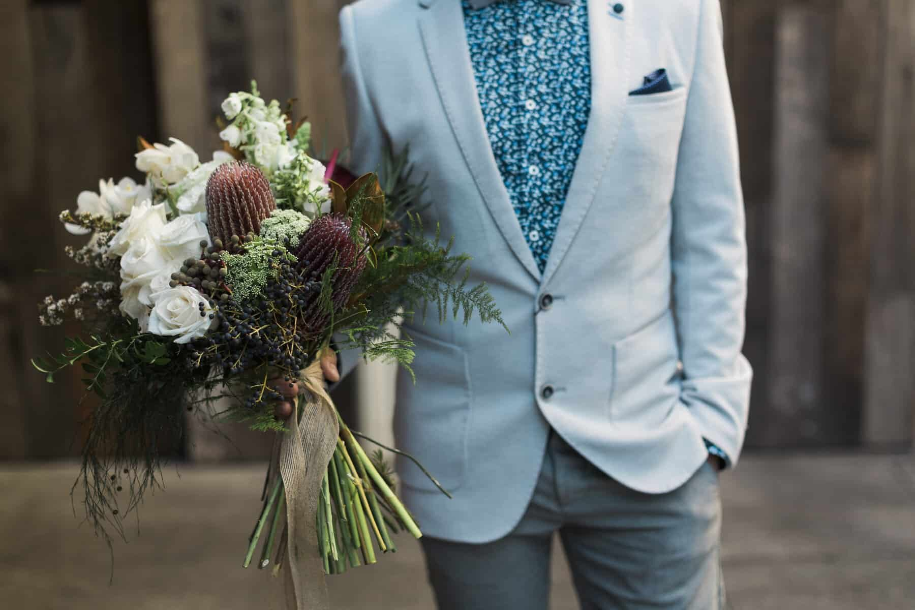 Stylish groom in pale blue blazer and floral print shirt