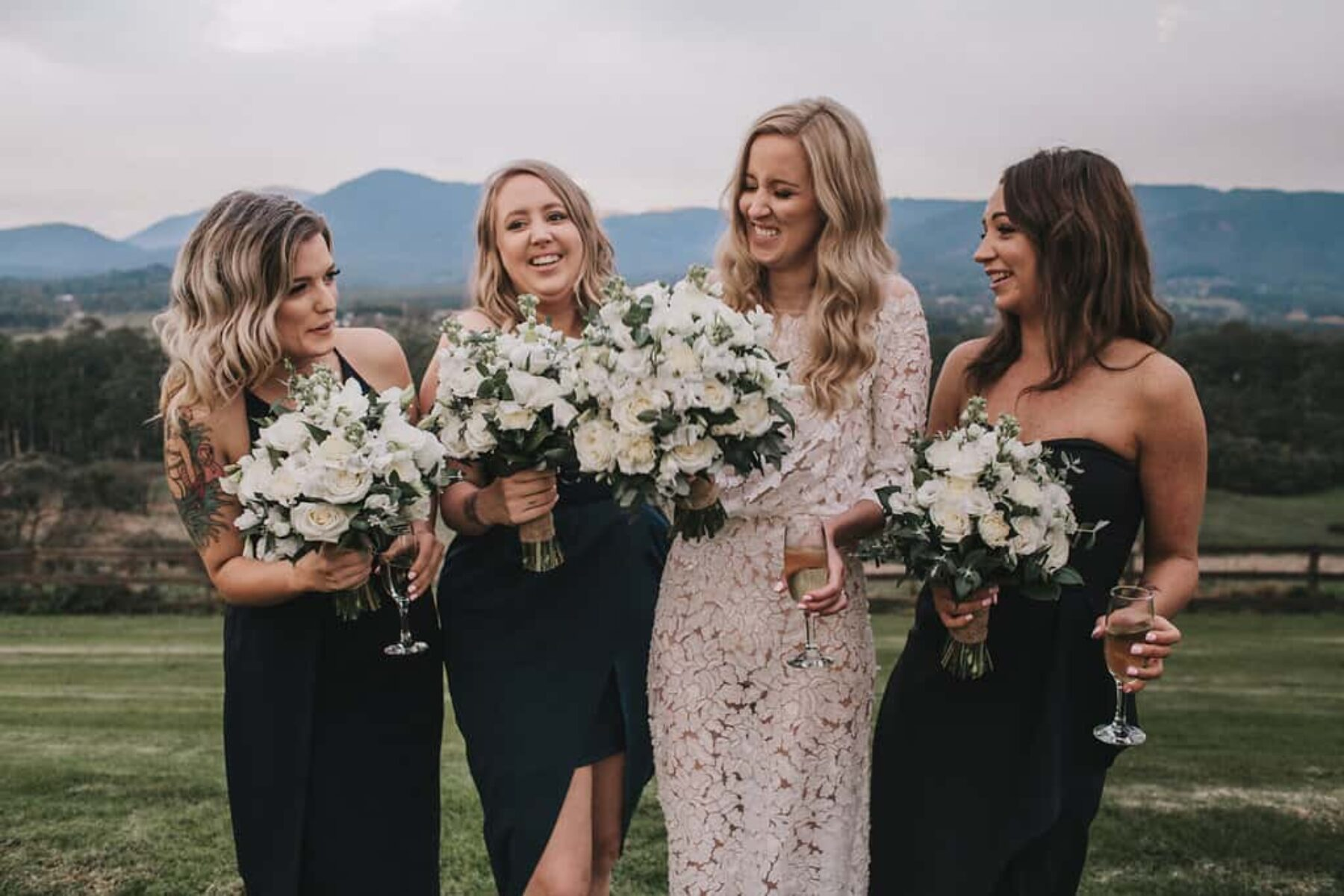 bridemaids in mixed navy dresses with green and white bouquets