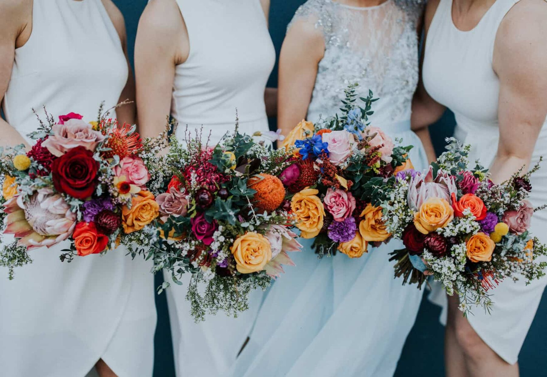 bridesmaids in modern white dresses with colourful bouquets