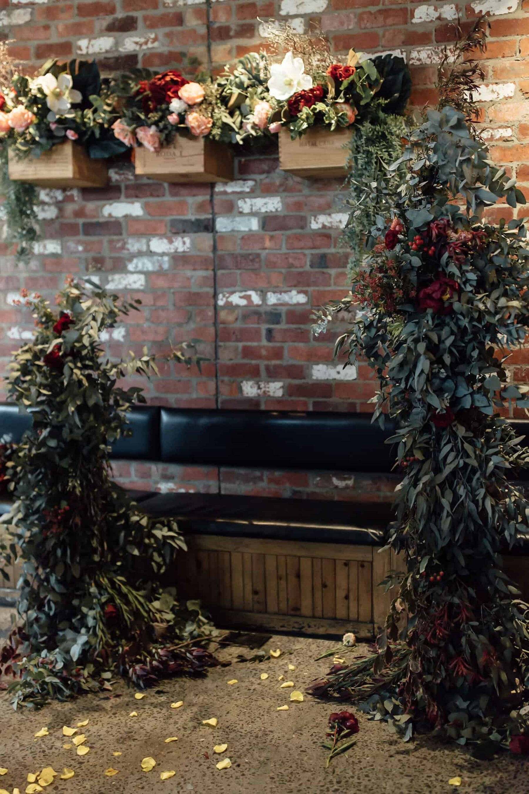 floral arch installation on exposed brick