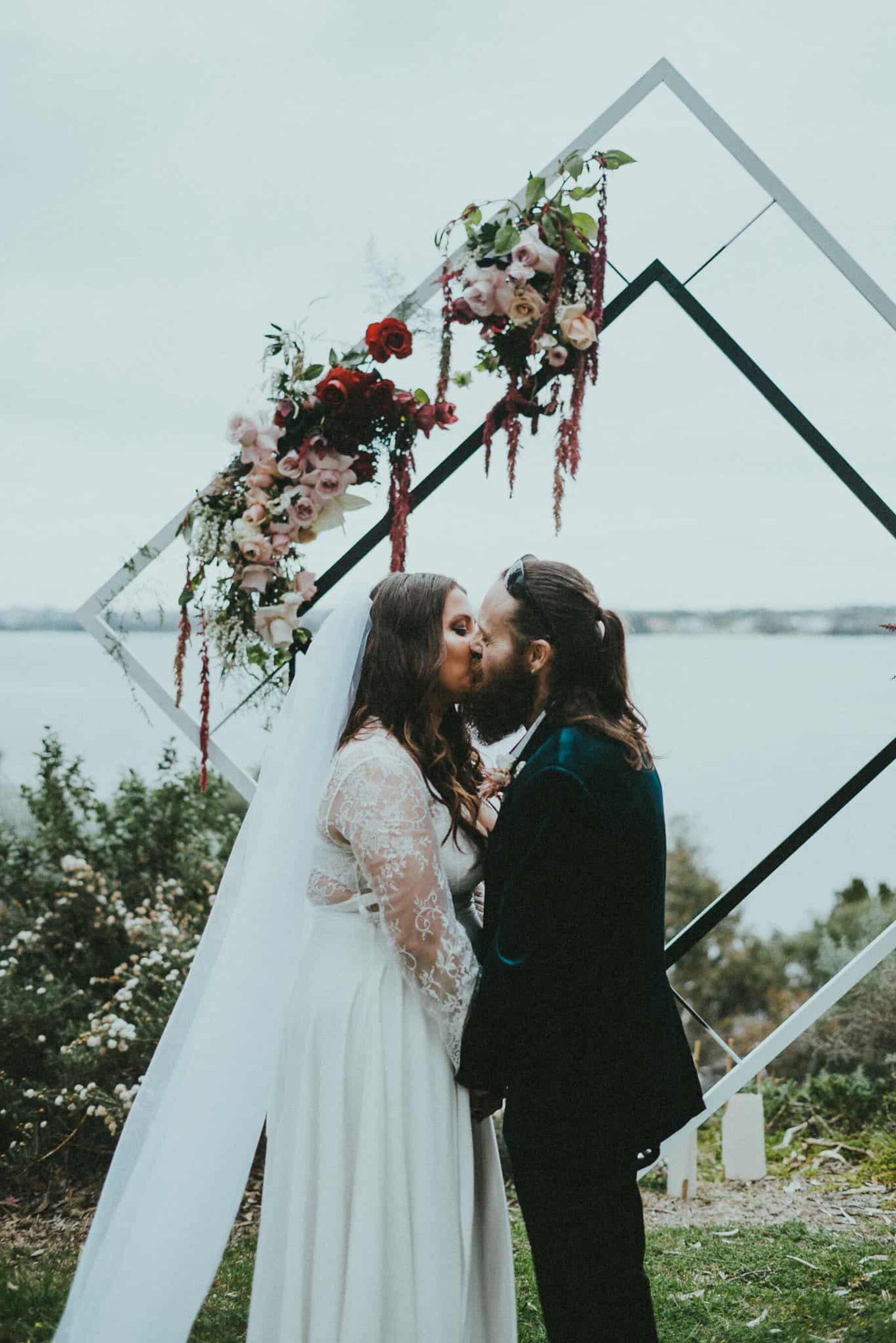 modern diamond wedding arbour with blush and burgundy flowers