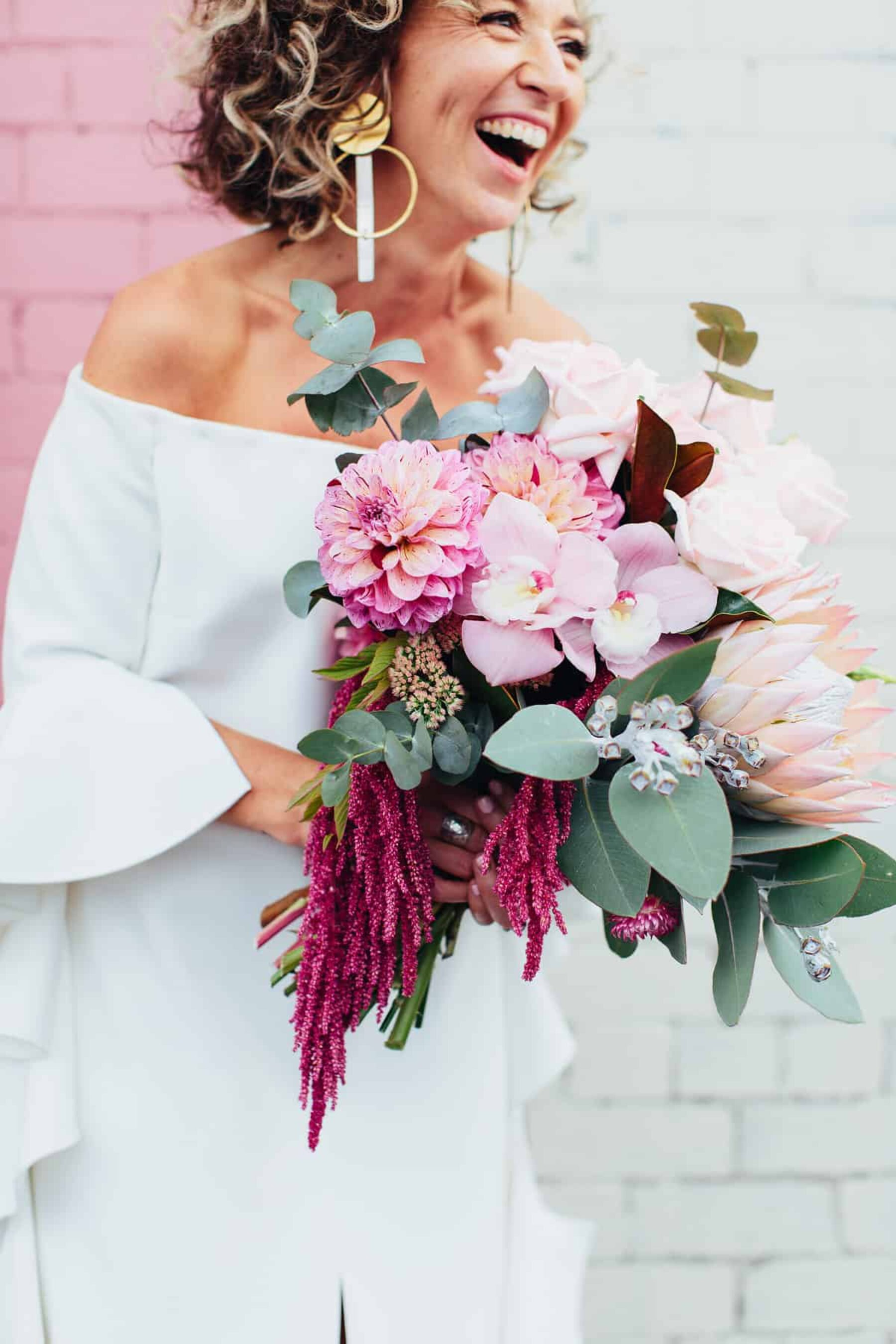 vibrant pink bouquet with with protea, amaranth and orchids