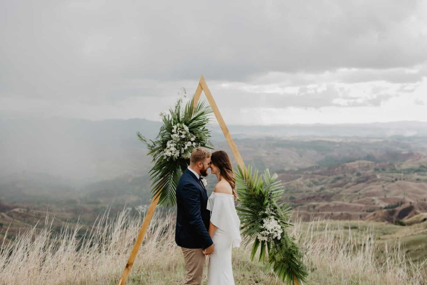 geometric triangle wedding arbour with tropical greenery