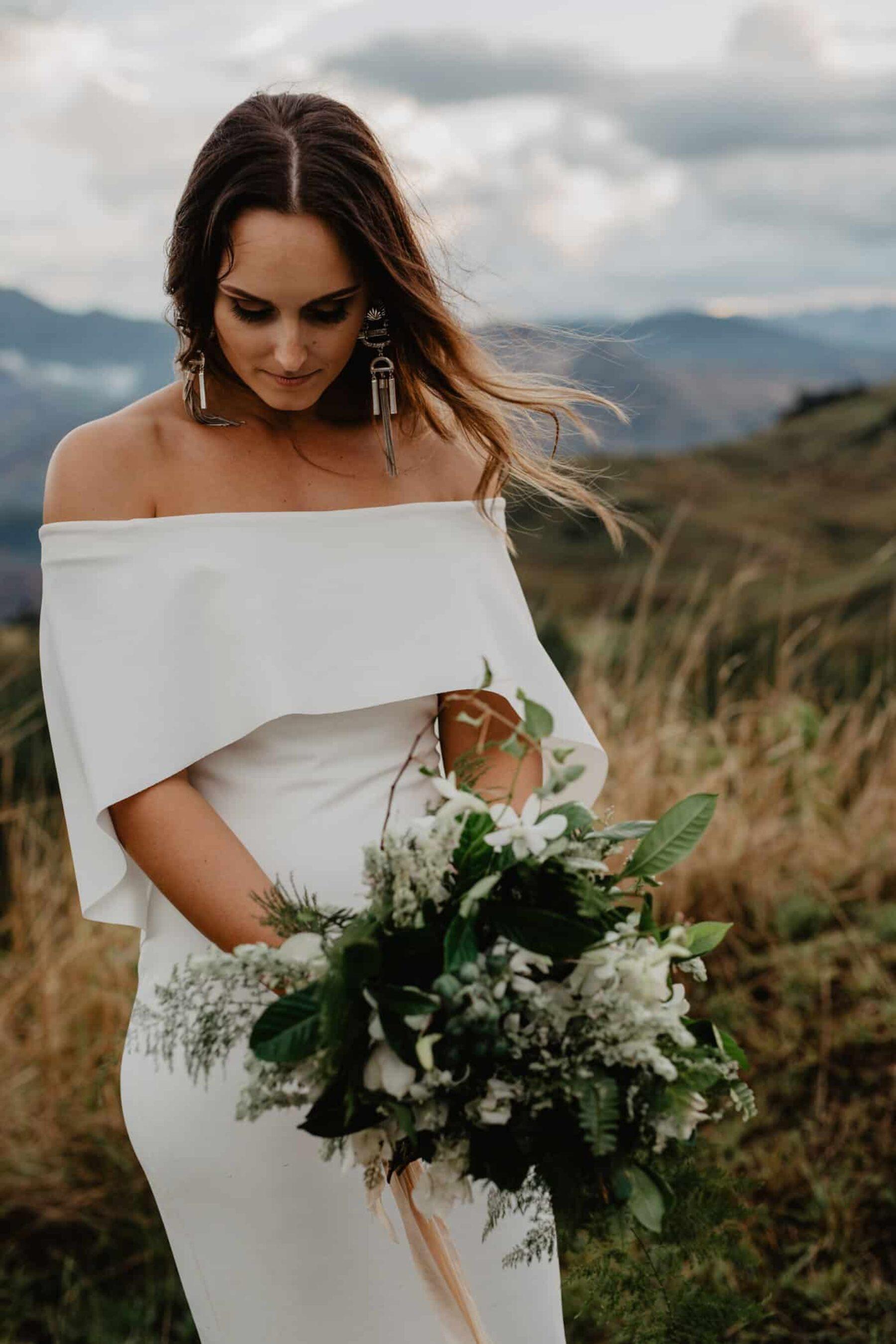 modern off-shoulder wedding dress with cape detail