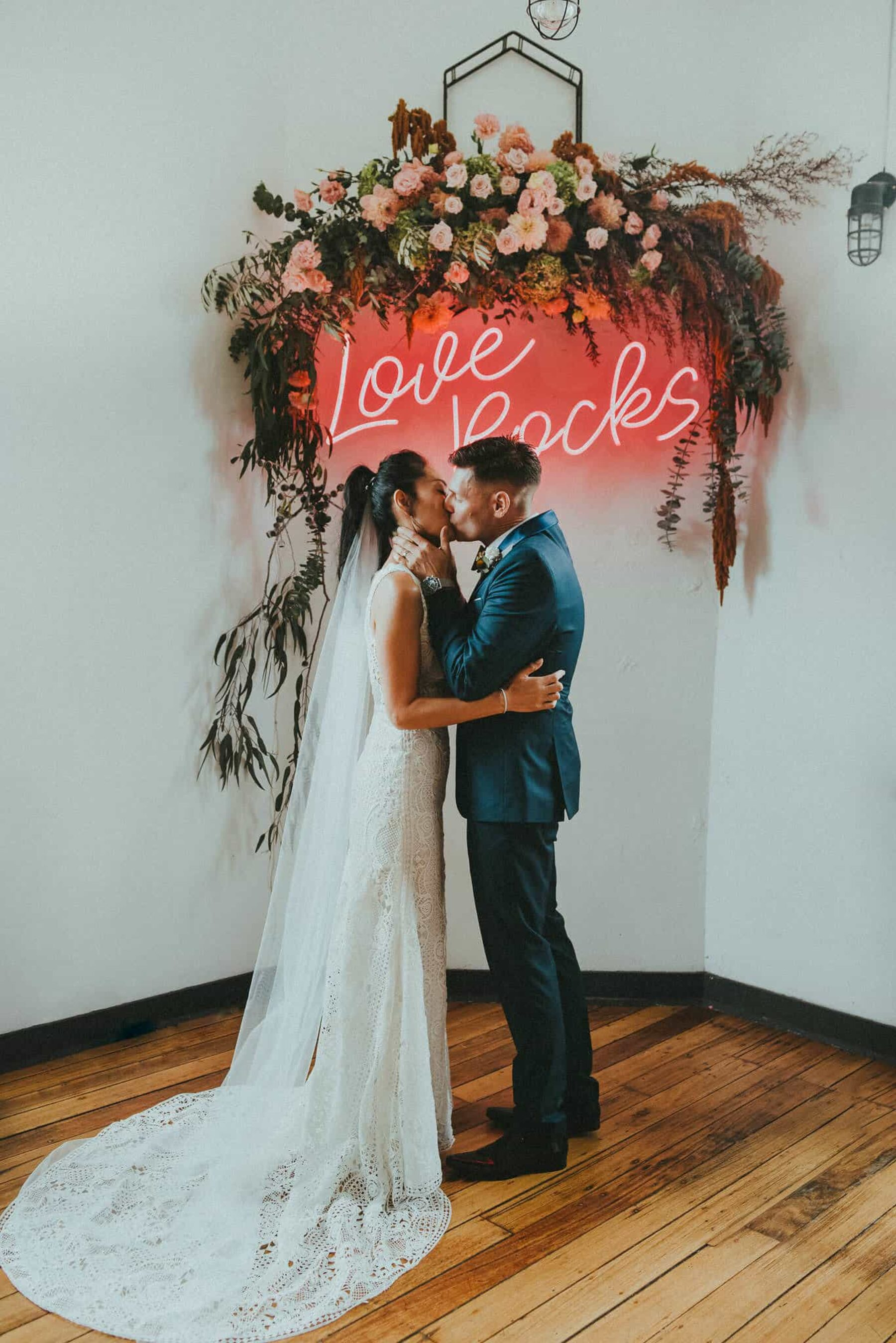 floral wedding backdrop with pink neon sign