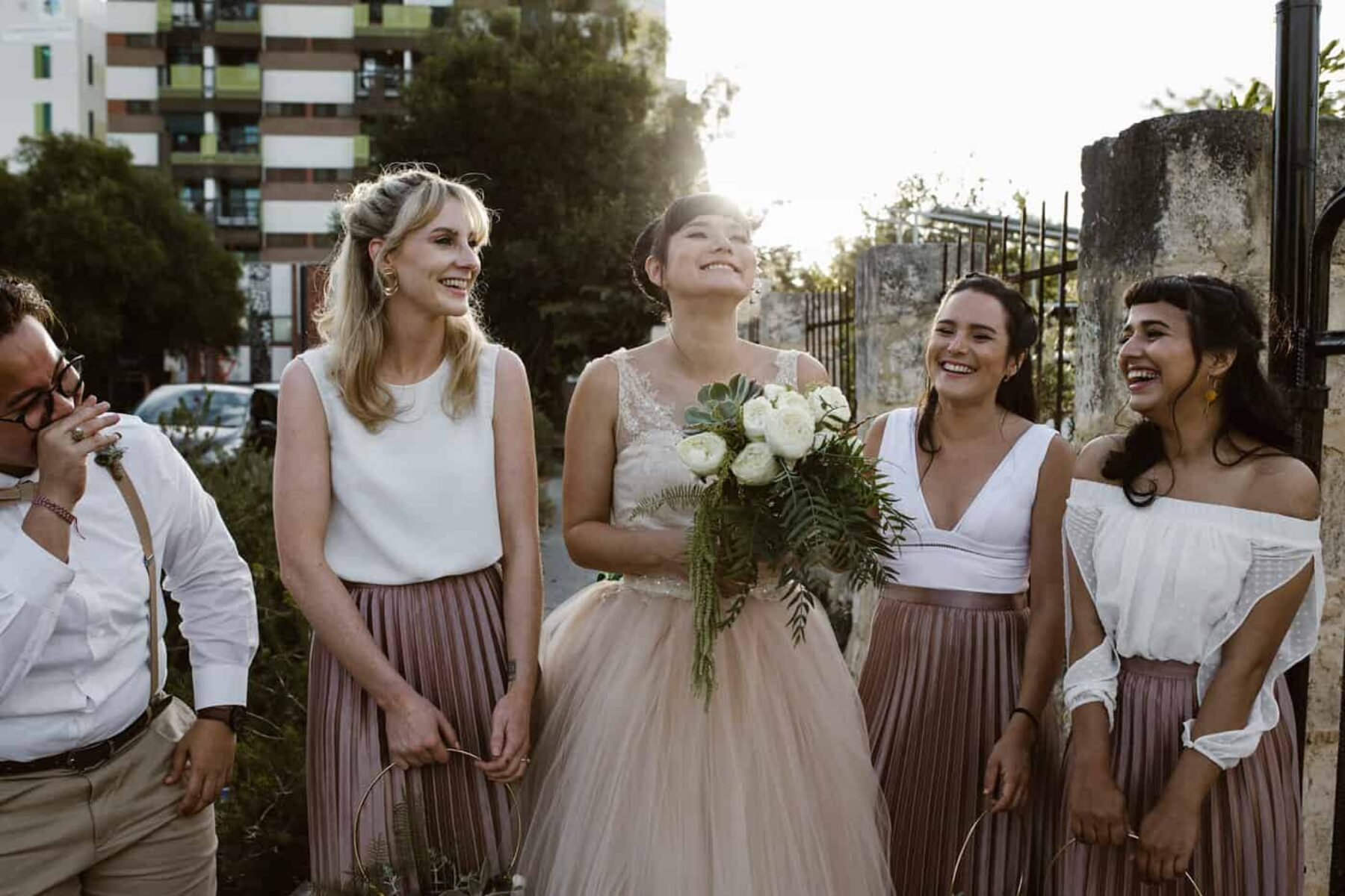 bridesmaids in dusty pink pleated skirts and white tops