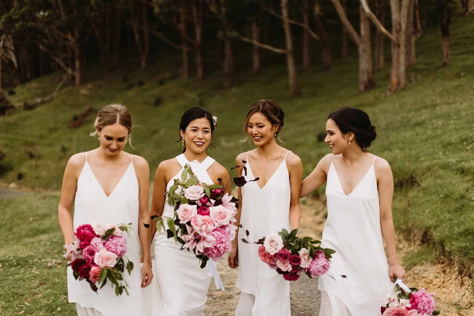 modern bridesmaids all in white with mixed pink bouquets