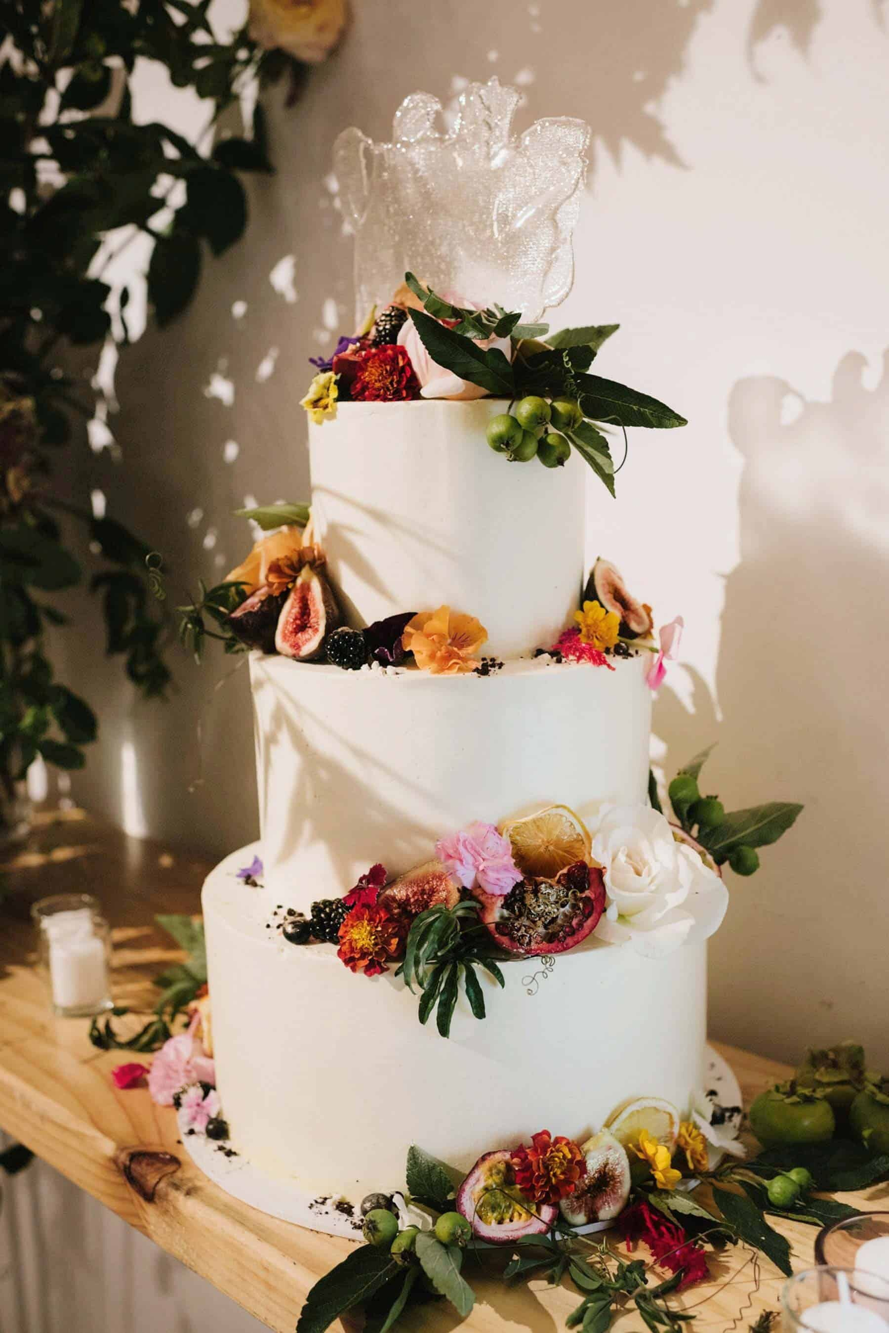 simple three tier wedding cake with fresh fruit and flowers