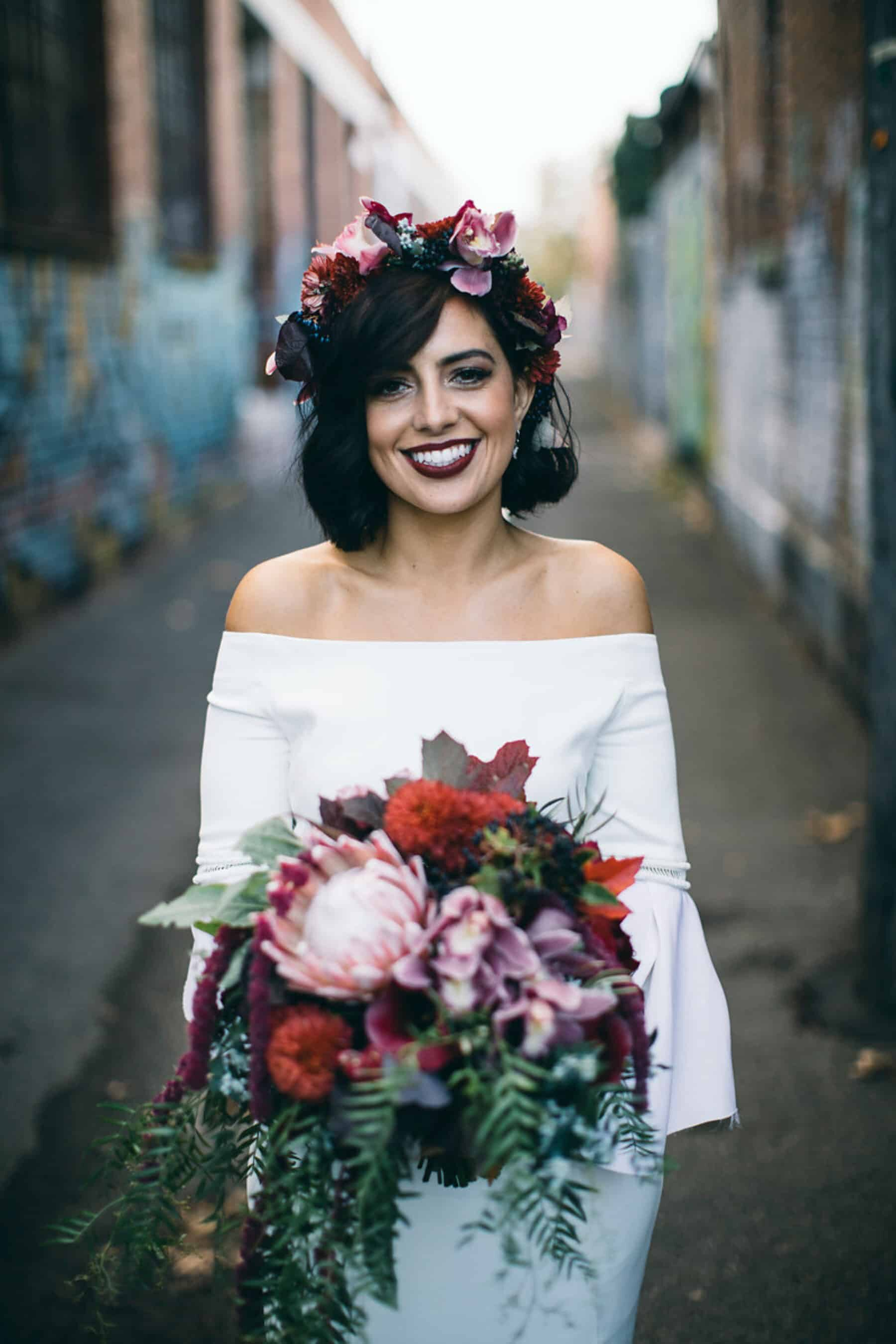modern bride in off-shoulder wedding dress and berry-toned flower crown