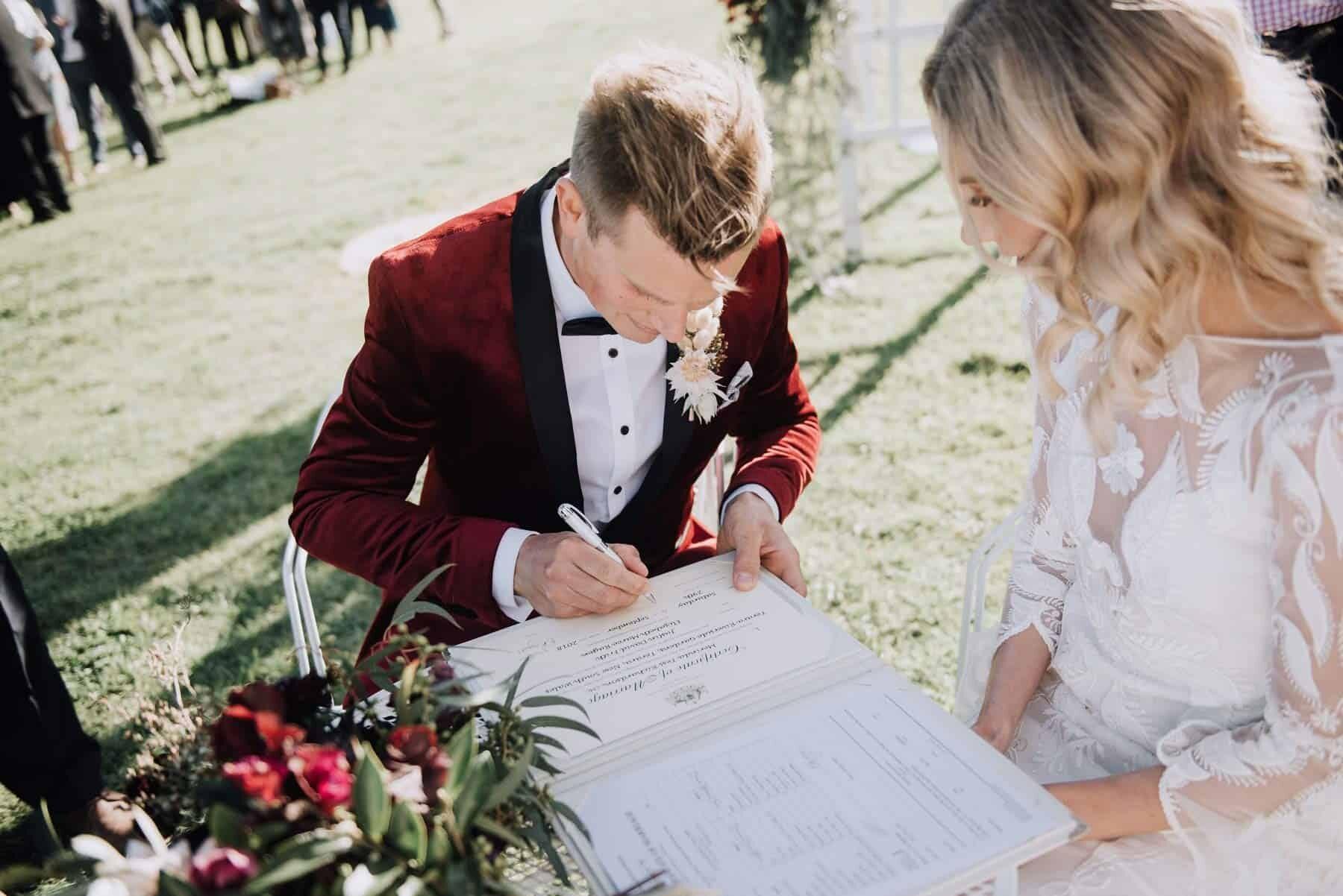 dapper groom in burgundy velvet jacket