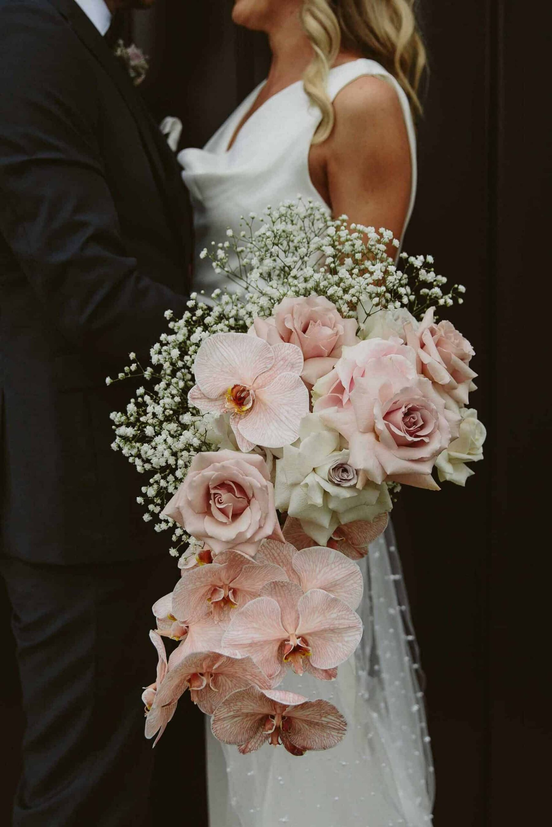 cascading blush bridal bouquet with orchids and quicksand roses