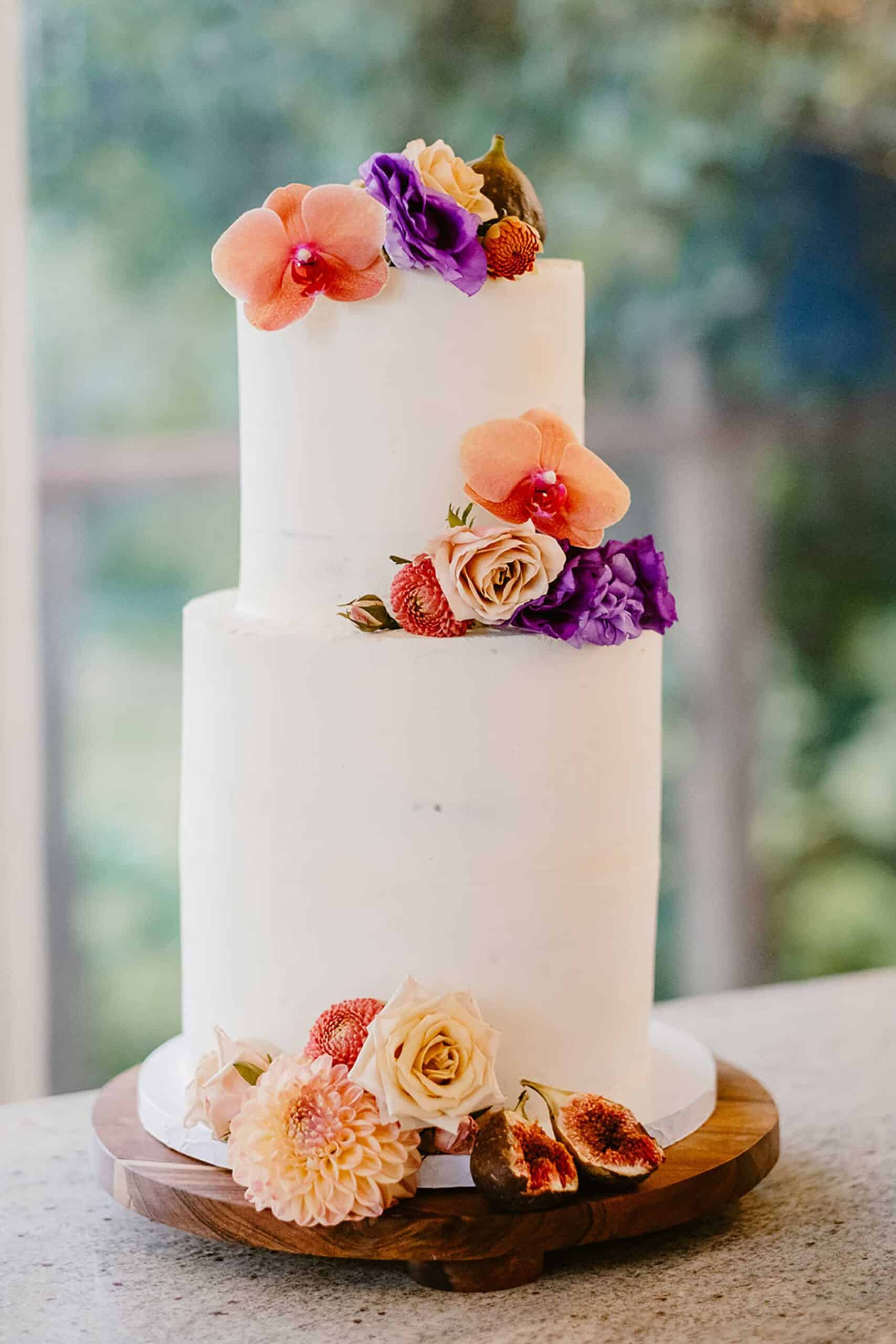 modern and minimal wedding cake with colourful fresh flowers