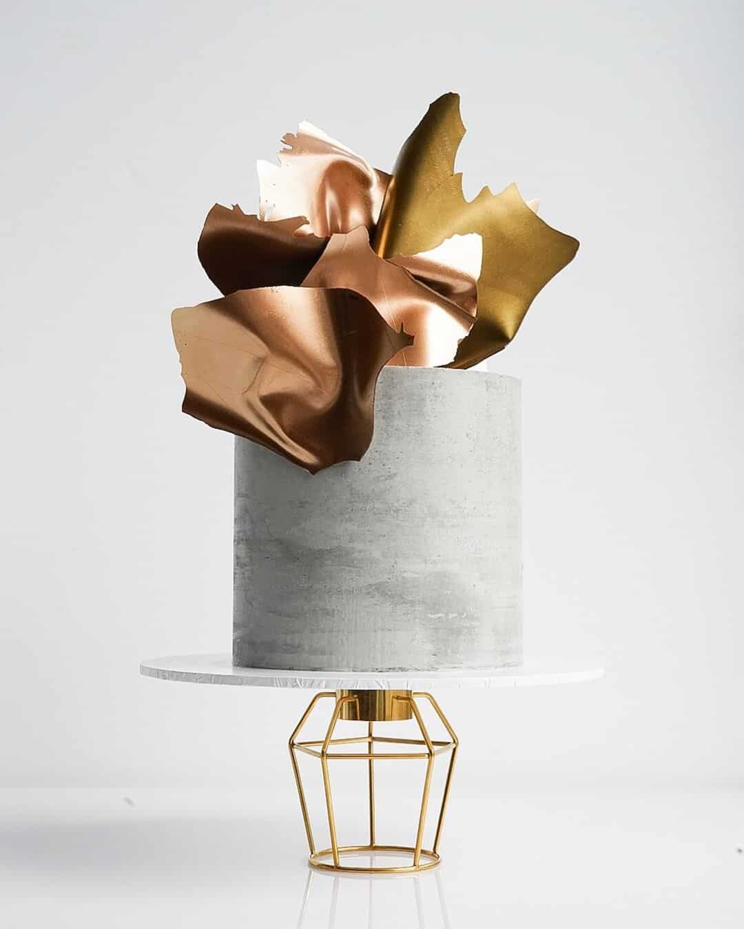 concrete cake with gold chocolate sails